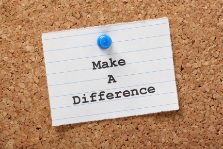 The phrase Make A Difference on a paper note pinned to a cork notice board.